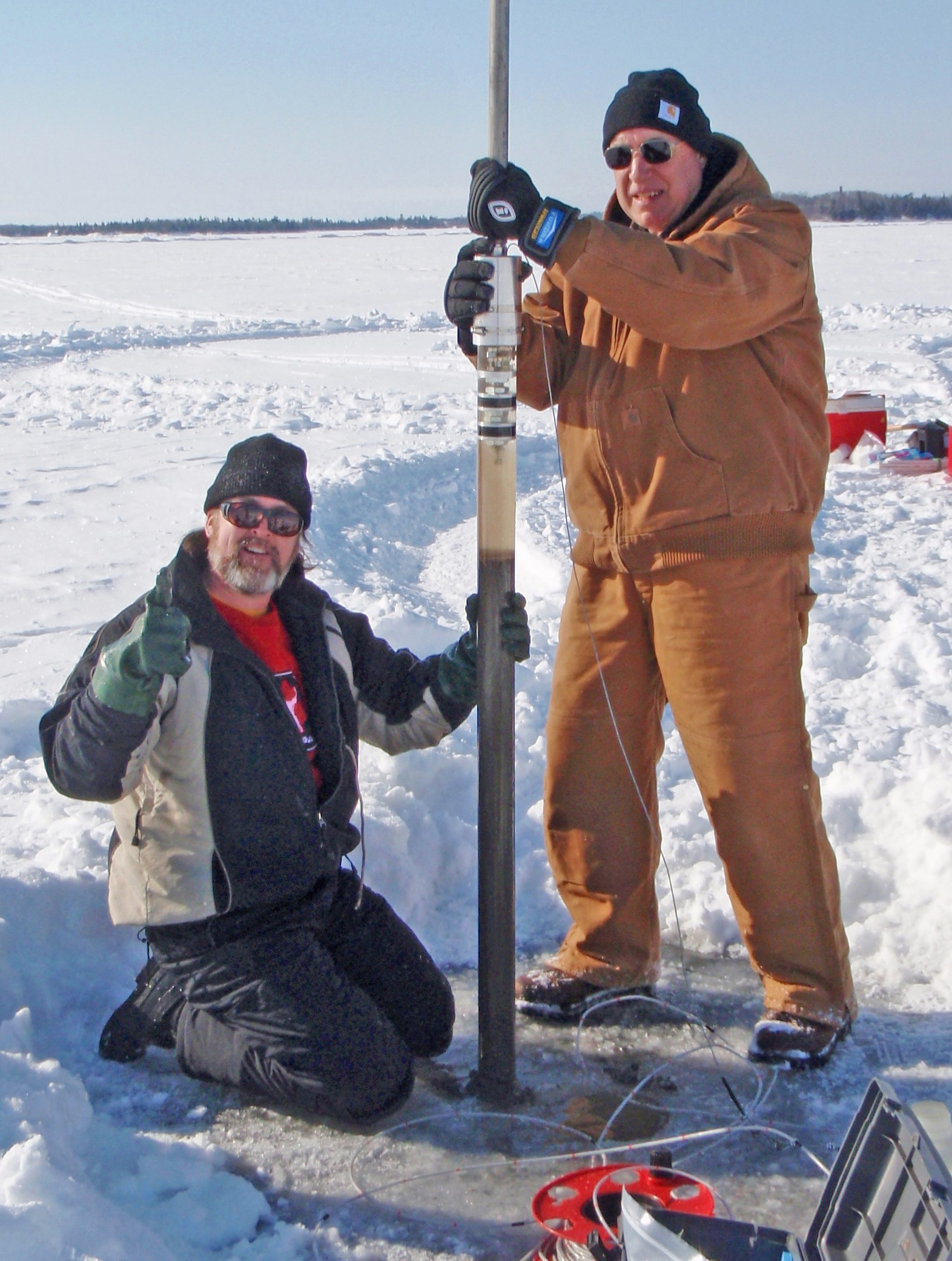 At left, Euan Reavie of the University of Minnesota. At right, Nolan Baratono, member of the Rainy-Lake of the Woods board and Forum Organizing Committee, with a sediment core taken from the bottom of the Big Traverse Bay for a historical nutrient loading study. Credit: Shawn Schottler, Science Museum of Minnesota