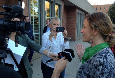 Sarah Harmer, at right, speaks to reporters outside the forum.