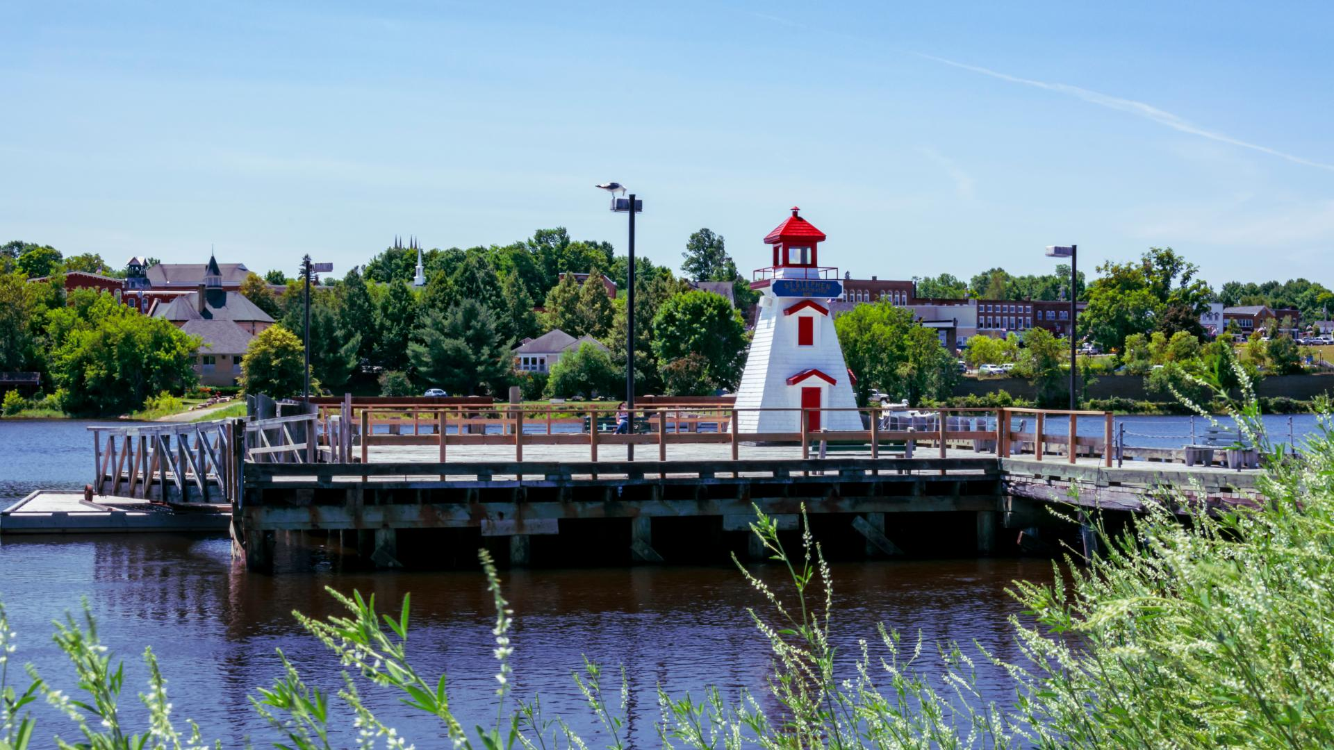 St. Stephen, New Brunswick, Canada. Saint Stephen's Lighthouse resides on the public wharf and above the waters of the St Croix river. The American town of Calais, Maine can be seen.