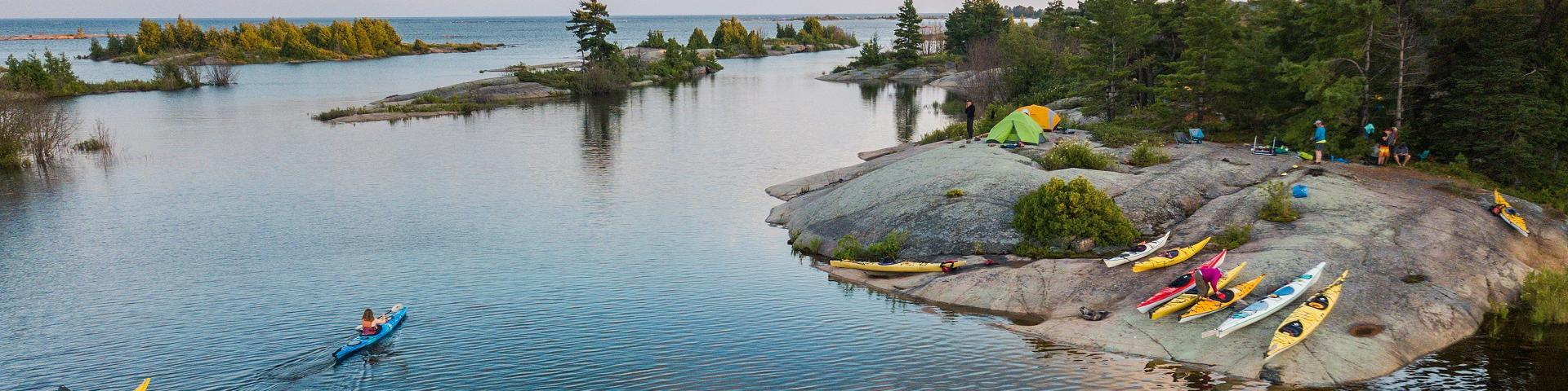 An aerial view of kayakers camping and paddling on the Great Lakes in northern Canada